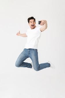 Imagem de jovem feliz animado posando isolado sobre uma parede branca, usando telefone celular, tire uma selfie mostrando copyspace.