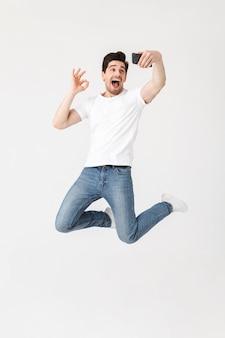 Imagem de jovem feliz animado posando isolado sobre uma parede branca, usando telefone celular, tire uma selfie mostrando o gesto certo.