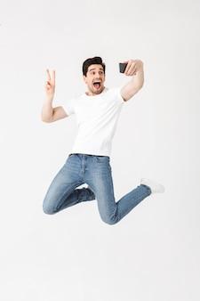 Imagem de jovem feliz animado posando isolado sobre uma parede branca, usando telefone celular, tire uma selfie mostrando um gesto de paz.