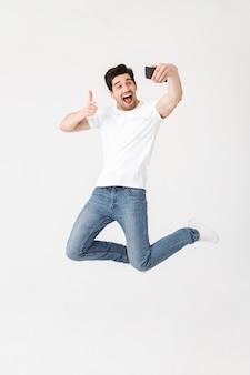 Imagem de jovem feliz animado posando isolado sobre uma parede branca, usando telefone celular, tome um selfie apontando.