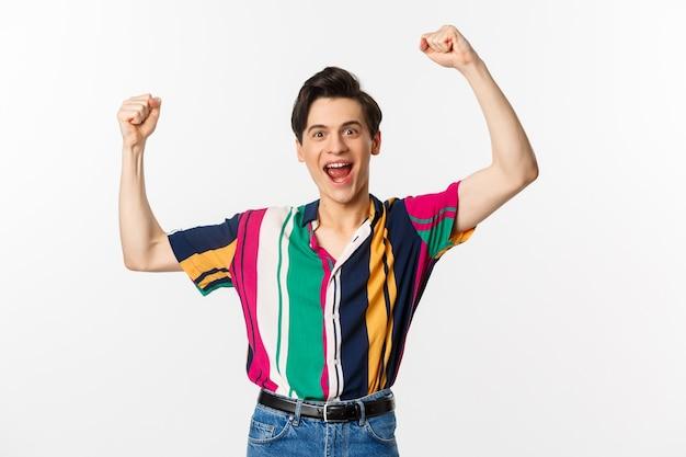Imagem de jovem feliz triunfando da vitória, comemorando a vitória, levantando as mãos em alegria e gritando sim, em pé sobre um fundo branco.