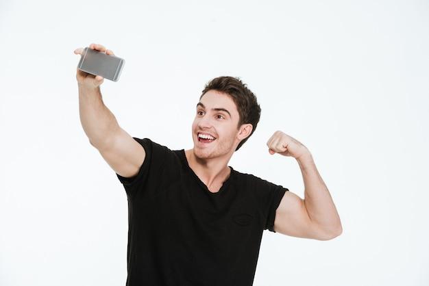Imagem de jovem feliz vestida com uma camiseta preta em pé sobre um fundo branco fazer uma selfie com bíceps ao lado de seu telefone.