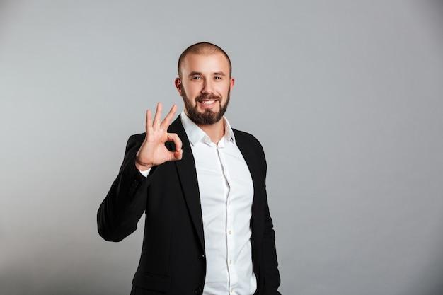 Imagem de jovem masculino em terno de negócio olhando na câmera e mostrando sinal okey, isolado sobre parede cinza