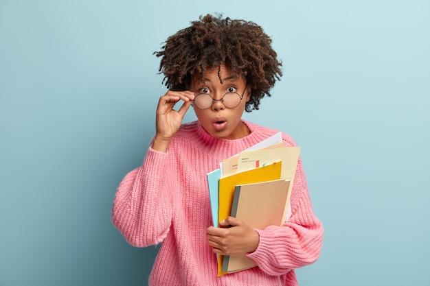 Imagem de jovem professora surpresa abre a boca sem palavras, segura alguns papéis e um bloco de notas