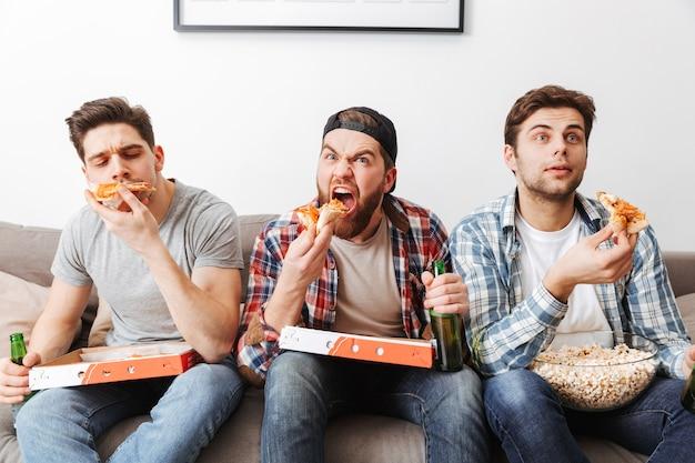 Imagem de jovens solteiros comendo pizza enquanto descansam em casa e assistindo a um jogo de futebol