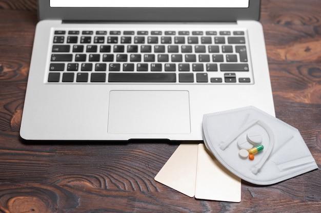 Imagem de laptop, cartão de ouro do banco, pílulas e equipamento de proteção contra coronavírus.