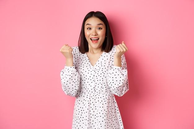 Imagem de linda mulher asiática vencendo, cerrar os punhos e dizer sim com uma cara feliz, triunfando e comemorando a vitória, em pé sobre um fundo rosa.