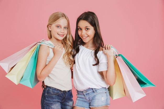 Imagem de lindas garotas morenas e loiras de 8 a 10 anos em roupas casuais, sorrindo para a câmera e segurando sacolas de compras coloridas, isoladas sobre fundo rosa