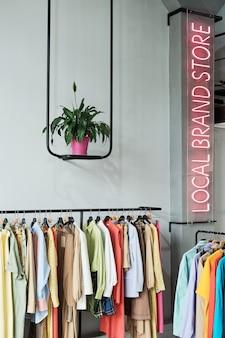Imagem de loja de roupas local com roupas da moda e uma placa iluminada na parede