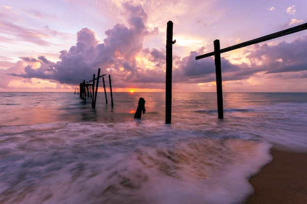 Imagem de longa exposição da paisagem do céu dramático com antigo poste de madeira no pôr do sol do mar ou fundo de paisagem do nascer do sol