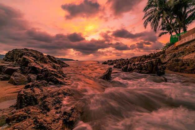 Imagem de longa exposição da paisagem do céu dramático com rochas no pôr do sol em primeiro plano ou nascer do sol sobre o fundo do cenário do mar.