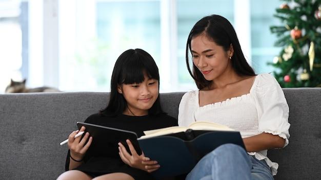 Imagem de mãe e filha usando tablet digital fazendo lição de casa em casa. conceito de educação online.