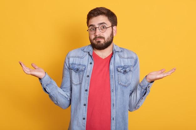 Imagem de magnético desamparado jovem encolher os ombros com os ombros, olhando diretamente levantando os braços