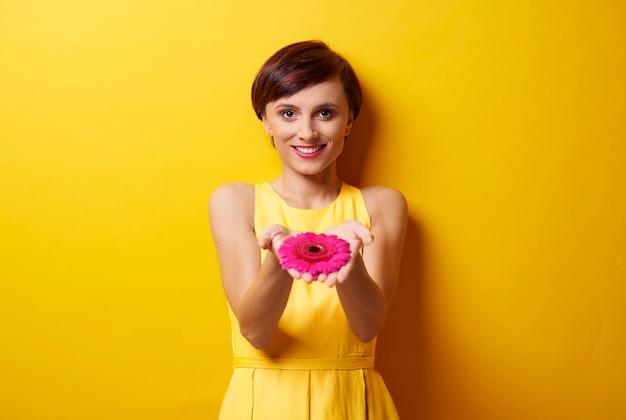 Imagem de mãos em forma de concha com uma flor