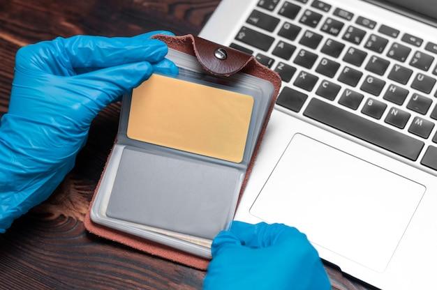 Imagem de mãos em luvas médicas na parede de um laptop.