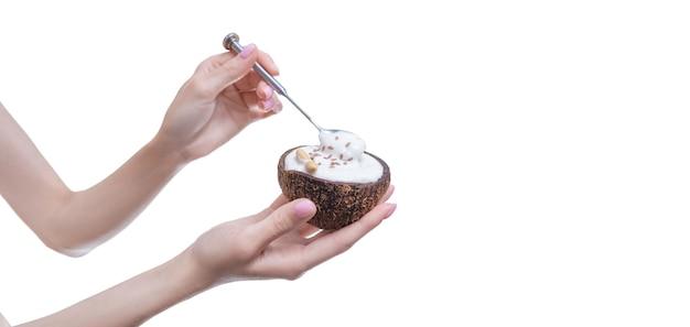 Imagem de mãos femininas com coco natural em que a sobremesa é servida. comida orgânica. mídia mista