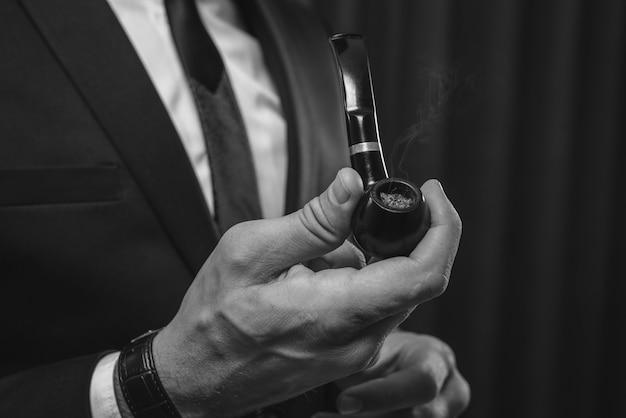 Imagem de mãos masculinas segurando um cachimbo. conceito de fumar tabaco. mídia mista