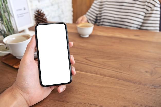 Imagem de maquete da mão de um homem segurando um celular preto com tela em branco com uma mulher tomando café em um café