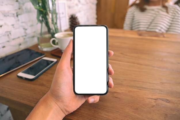 Imagem de maquete da mão de um homem segurando um celular preto com uma tela em branco com uma mulher sentada em um café