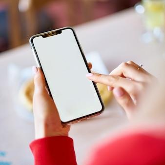 Imagem de maquete da mão de uma mulher segurando o celular branco com uma tela em branco na coxa com a parede da mesa de madeira no café moderno