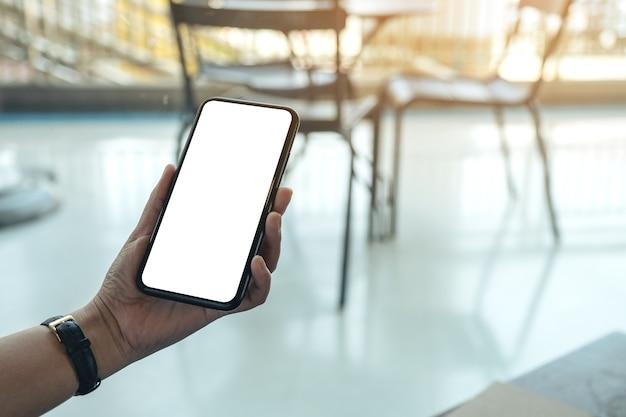 Imagem de maquete da mão de uma mulher segurando um telefone celular preto com uma tela em branco