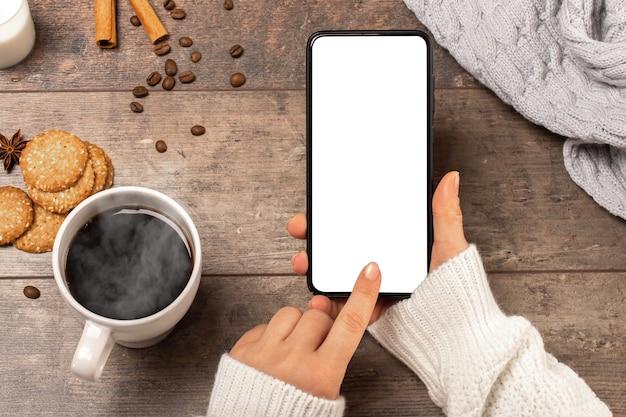 Imagem de maquete das mãos de uma mulher segurando um celular com tela em branco