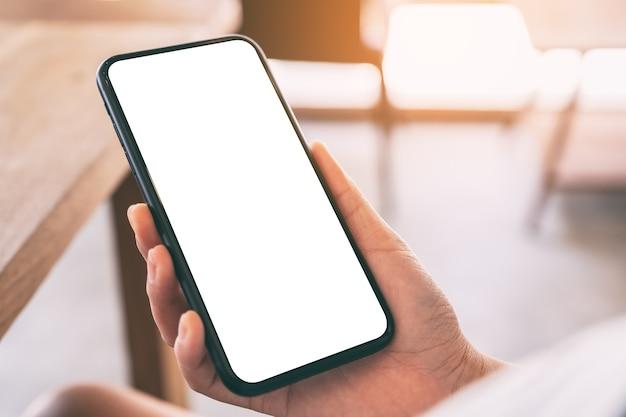 Imagem de maquete das mãos de uma mulher segurando um celular preto com uma tela em branco em um café