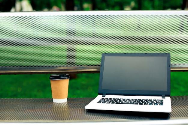 Imagem de maquete de laptop com tela preta em branco e xícara de café no banco de metal no parque natural ao ar livre. trabalho freelance.