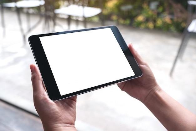 Imagem de maquete de mãos de mulher segurando preto tablet pc com tela branca de mesa em branco no café
