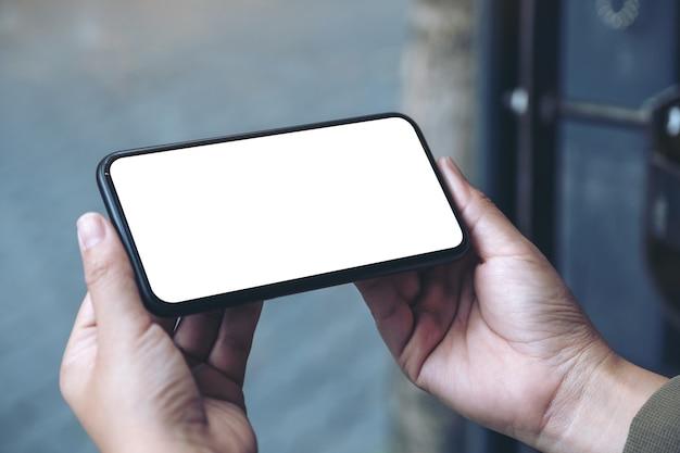 Imagem de maquete de mãos segurando um celular preto com a tela em branco horizontalmente