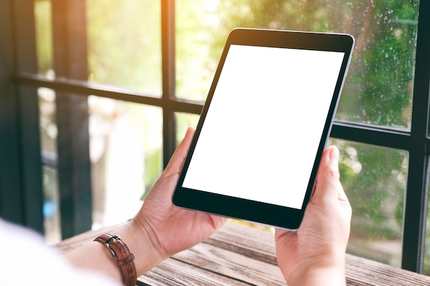 Imagem de maquete de mãos segurando um tablet pc preto com uma tela de desktop em branco