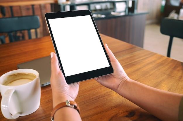 Imagem de maquete de mãos segurando um tablet pc preto com uma tela em branco e uma xícara de café na mesa de madeira