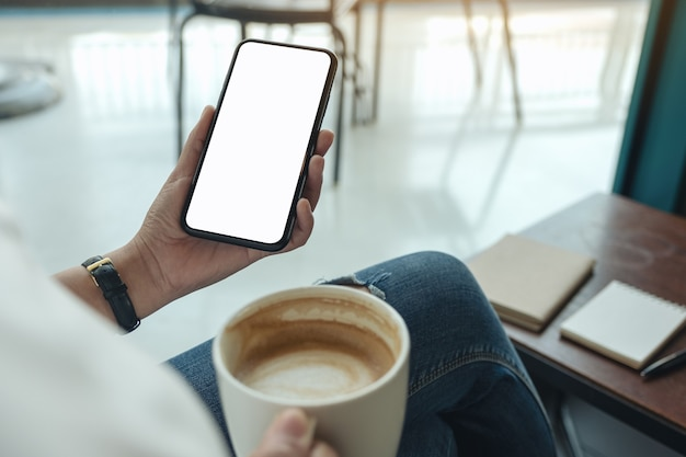 Imagem de maquete de mãos segurando um telefone celular branco com tela em branco enquanto bebe café