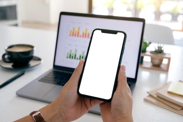 Imagem de maquete de mãos segurando um telefone celular preto com tela em branco enquanto usa um laptop no escritório