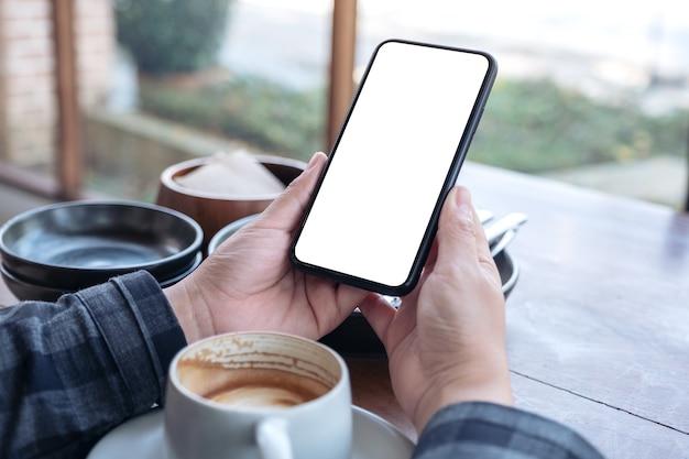 Imagem de maquete de mãos segurando um telefone celular preto com uma tela em branco e uma xícara de café em cima da mesa