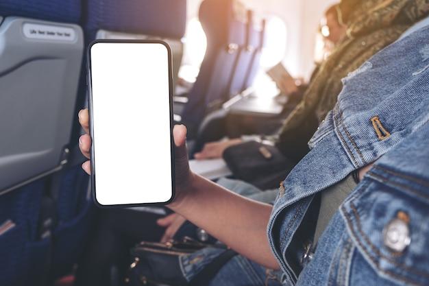 Imagem de maquete de mulher segurando e mostrando um telefone inteligente preto com tela em branco na cabine