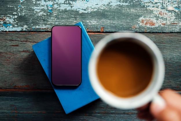 Imagem de maquete de smartphone com traçado de recorte. usando o celular enquanto bebe café e lê livro