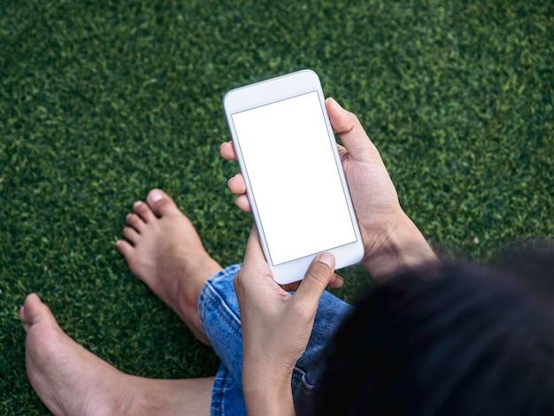 Imagem de maquete de telefone. tela em branco branca no celular nas mãos da mulher no fundo verde da grama artificial. mão segurando um smartphone branco com tela vazia.