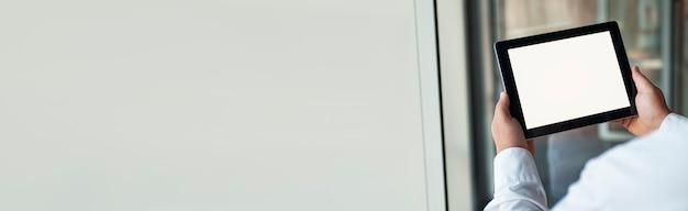 Imagem de maquete de um homem segurando o tablet preto na mão com uma tela em branco sobre fundo na porta.