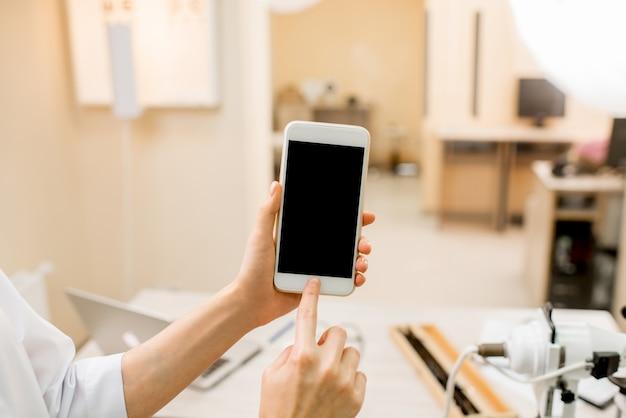 Imagem de maquete de um telefone inteligente no fundo do consultório oftalmológico