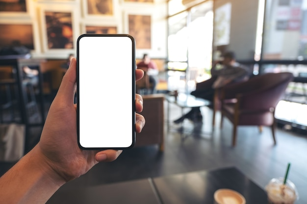 Imagem de maquete de uma mão segurando e mostrando um celular preto com uma tela em branco em um café