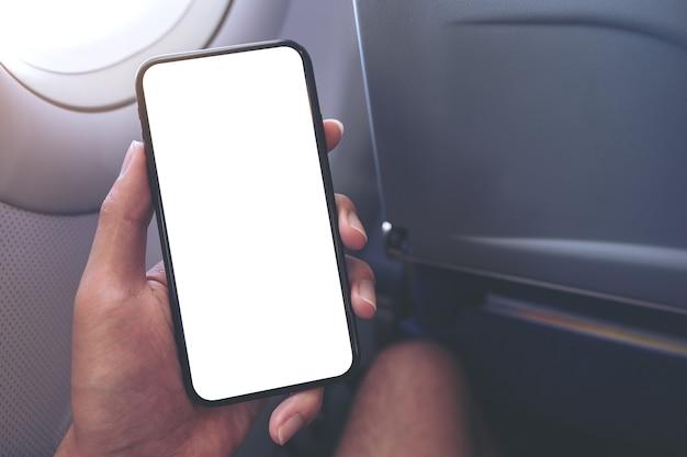 Imagem de maquete de uma mão segurando um smartphone preto com uma tela em branco ao lado de uma janela de avião