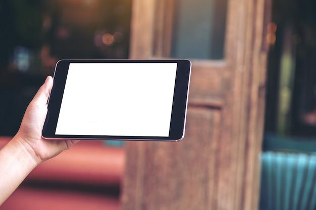 Imagem de maquete de uma mão segurando um tablet pc preto