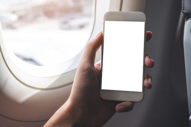 Imagem de maquete de uma mão segurando um telefone inteligente branco com tela em branco ao lado de uma janela de avião