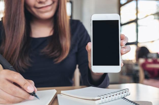 Imagem de maquete de uma mulher asiática segurando e mostrando um celular branco