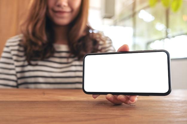Imagem de maquete de uma mulher segurando e mostrando um celular branco com tela em branco horizontalmente em uma mesa de madeira