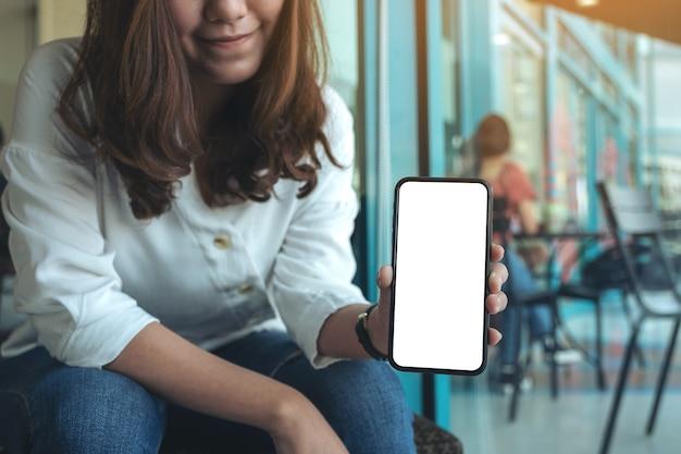 Imagem de maquete de uma mulher segurando e mostrando um celular preto com uma tela em branco em um café