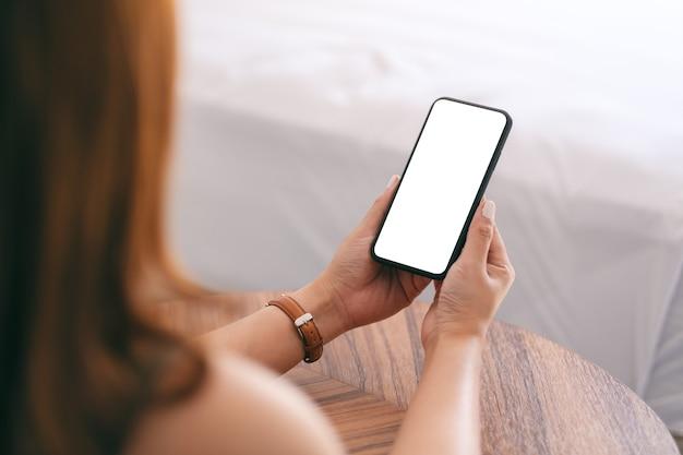 Imagem de maquete de uma mulher segurando e usando um telefone celular com tela em branco, enquanto está sentada ao lado da cama