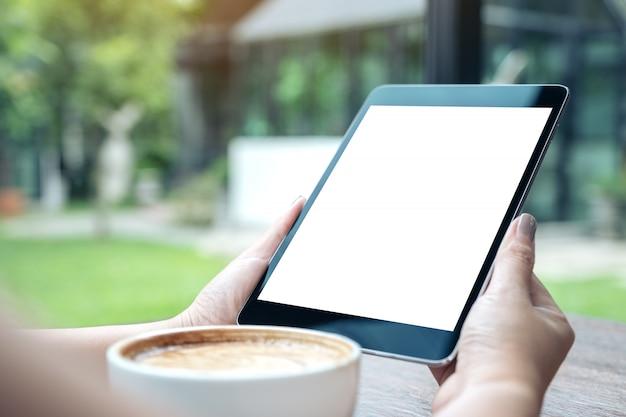 Imagem de maquete de uma mulher segurando preto tablet pc com tela em branco branca com uma xícara de café na mesa