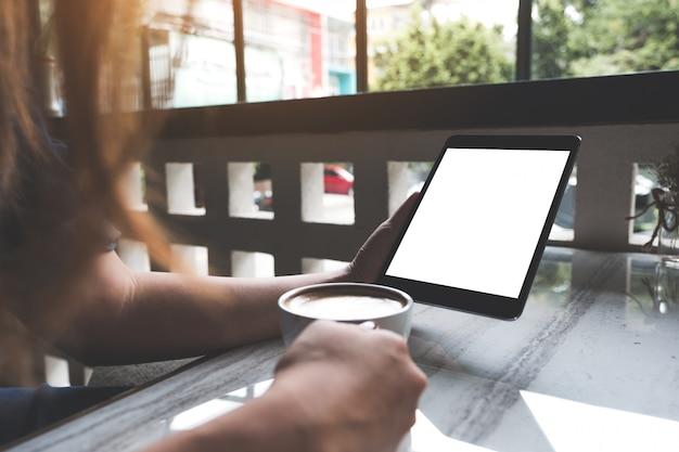 Imagem de maquete de uma mulher segurando preto tablet pc com tela em branco branca enquanto bebe café no café
